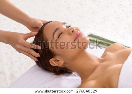 Asian young woman enjoying scalp massage - stock photo