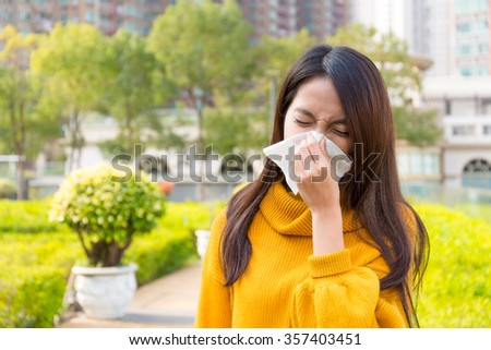 Asian Young Woman got allergy of nose when standing outdoor - stock photo