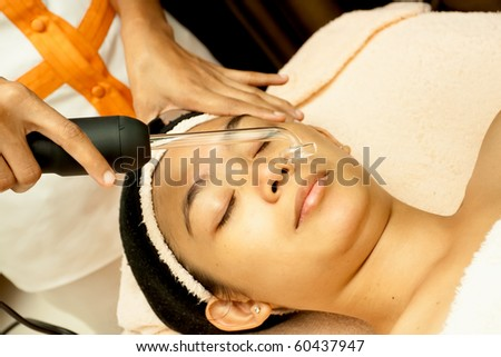 Asian young woman having facial treatment at beauty clinic - stock photo