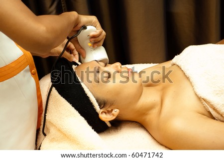 Asian young woman having facial treatment with collagen serum - stock photo