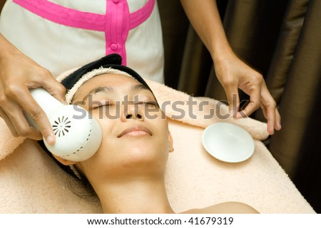 asian young woman having her face being applied by collagen serum in facial treatment session at beauty clinic - stock photo