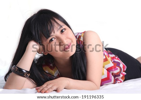 asian young woman lie down on bed smiling - stock photo