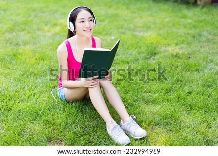 asian young woman listening music through headset and reading book in park - stock photo