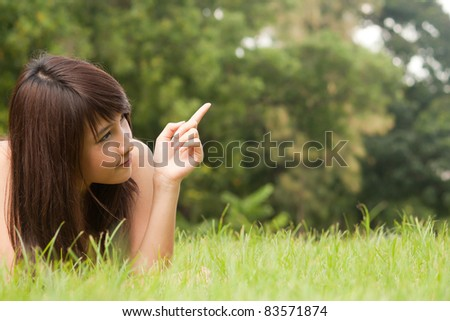 Asian young woman lying on the green grass and pointing up to something - stock photo