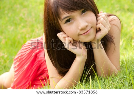 Asian young woman lying on the green grass and smiling