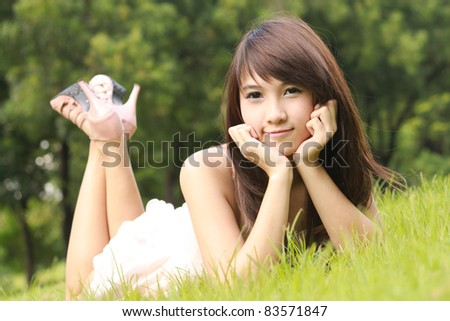 Asian young woman lying on the green grass and smilling - stock photo