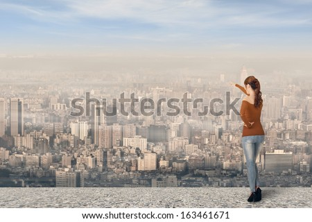 Asian young woman point somewhere over the city, full length portrait. - stock photo