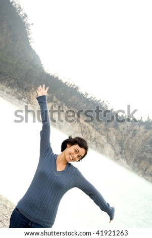 asian young woman raise and spread her arms, expressing her joy in outdoor scene - stock photo
