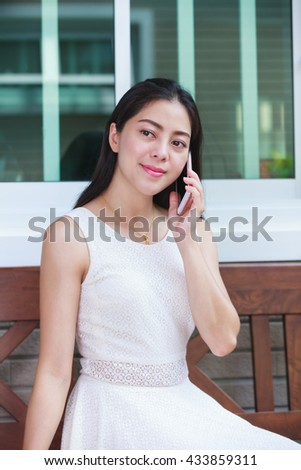 Asian young woman talking on mobile phone outside on home summer. Active lifestyle happy young adult on relaxing day at home. - stock photo