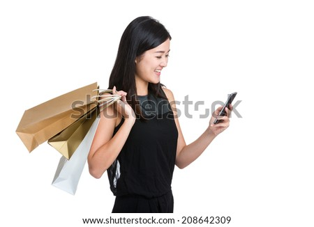 Asian young woman use mobile phone with shopping bag - stock photo