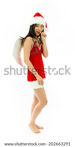 Asian young woman wearing Santa costume dressed up as an angel with finger in mouth isolated on white background