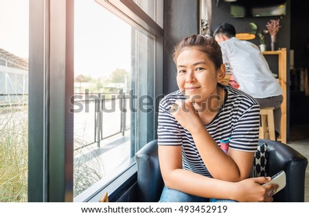 Asian young woman while relaxing sitting with her cell telephone in coffee shop. Young charming woman enjoying and smiling with mobile phone in cafe.