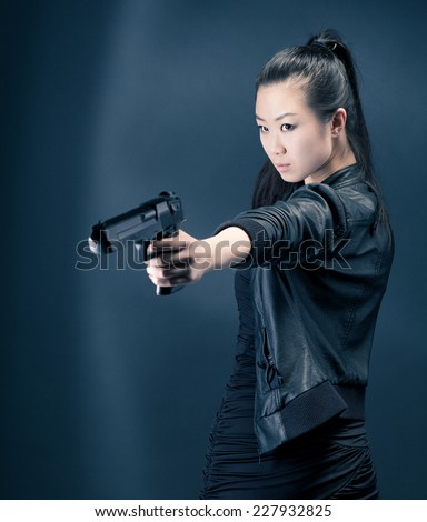Asian young woman with a gun. - stock photo