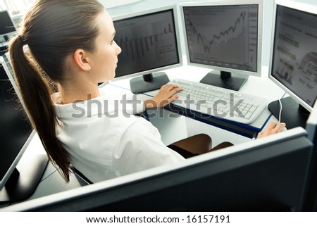 Aside view of student sitting at computer with serious expression and looking at monitor of computer - stock photo