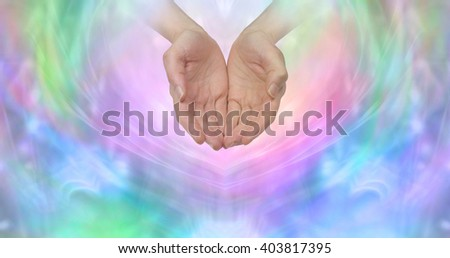 Ask and it is Given - female cupped hands emerging from a wispy pastel colored background with plenty of copy space ideal for a fund raising campaign  - stock photo