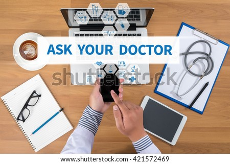 ASK YOUR DOCTOR Doctor working at office desk and using a mobile touch screen phone, computer and medical equipment all around, top view, coffee - stock photo