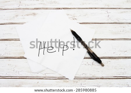 Asking for Help, Two napkins with the word Help with a pen over a distressed wood background - stock photo