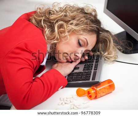 Asleep at the office - woman sleeping despite energy pills - stock photo