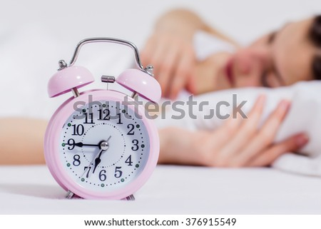 Asleep caucasian young woman with alarm clock in focus.