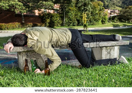 Asleep or drunk young man, outdoors on a park bench with beer bottles - stock photo