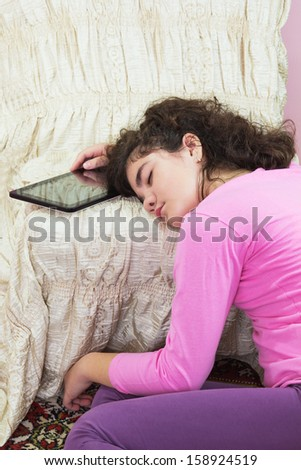 Asleep young girl with a tablet computer - stock photo