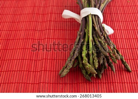 Asparagus acutifolius ,  freshly picked wild asparagus photographed on a red background - stock photo