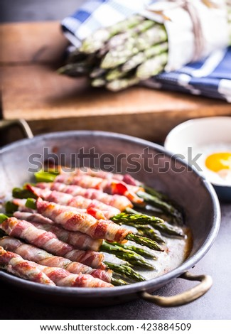 Asparagus. Asparagus and roll bacon. Grilled asparagus with rolled bacon and fried egg. Fried old pan full of rolled bacon with green asparagus and fried egg. - stock photo