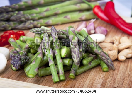 Asparagus, cashews, garlic and hot peppers on cutting board ready for a stir fry. - stock photo