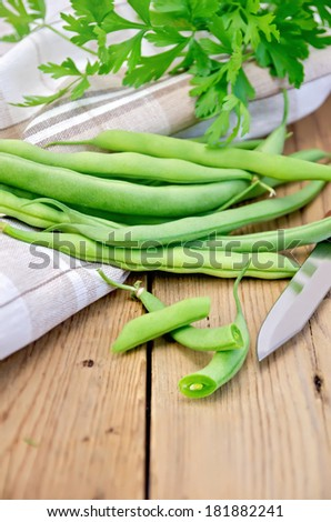 Asparagus green beans, napkin, knife, parsley on a wooden boards background - stock photo