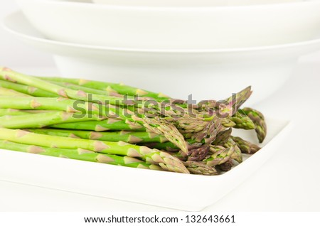 Asparagus on a white plate with bowls in background - stock photo