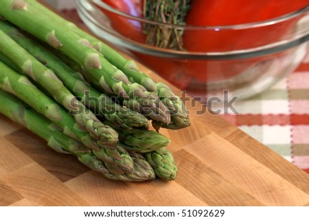 asparagus on fine wood cutting board with red peppers on a bowl