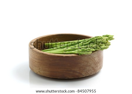 Asparagus on wood bowl isolated in white background - stock photo