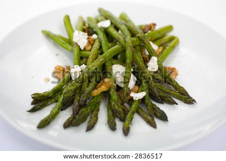 Asparagus roasted in olive oil with goat cheese and crushed walnuts on a white plate. A tasty side dish to any meal. - stock photo