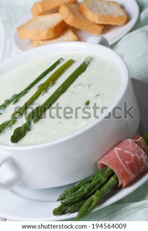 Asparagus soup closeup in white bowl and croutons. vertical  - stock photo