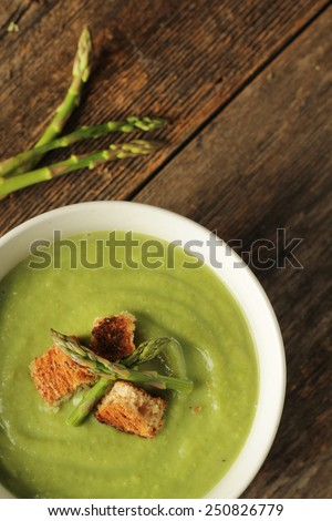 Asparagus soup on a wooden background - stock photo