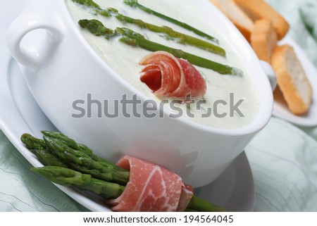 Asparagus soup with ham closeup in white bowl and croutons. horizontal   - stock photo