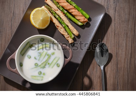 Asparagus soup with lemon and bread sticks on wooden table - stock photo