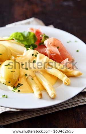 Asparagus spears , ham and chives served with a topping of creamy mayonnaise and potatoes for a delicious meal - stock photo
