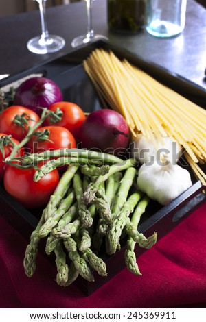 Asparagus, tomatoes,onions garlic, and linguini for making an Italian linguinie meal - stock photo