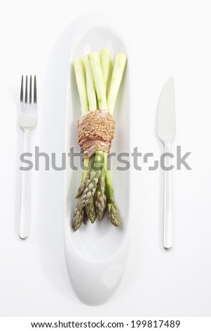 Asparagus with ham and sesame in glass on white background - stock photo