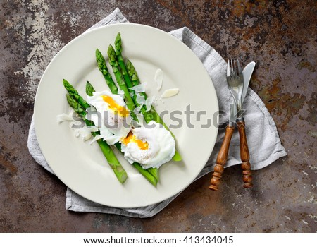Asparagus with poached eggs seasoned with parmesan, top view - stock photo