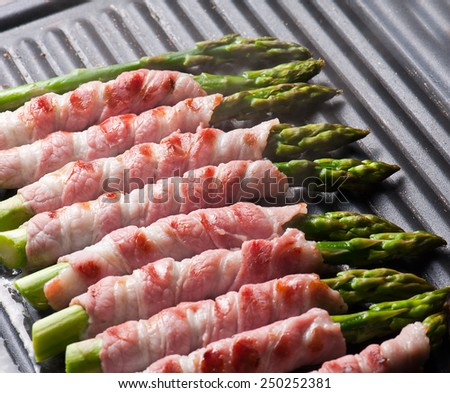 Asparagus wrapped in bacon on the hot pan - stock photo