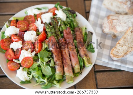 Asparagus wrapped in bacon with salad - stock photo
