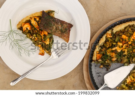Asparagus zucchini salmon quiche with homemade shortcrust pastry and dill in backing tray with crispy salmon skin, shiny fork on white plate - stock photo