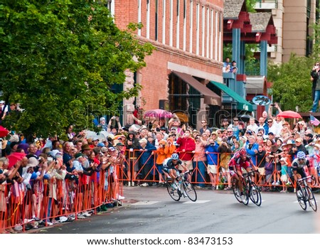 ASPEN, CO - AUG. 24: A packed crowd cheers George Hincapie (C) on his final sprint to the finish winning the Queen Stage of USA Pro Cycling Challange in historic downtown Aspen, CO. on Aug 24, 2011 - stock photo