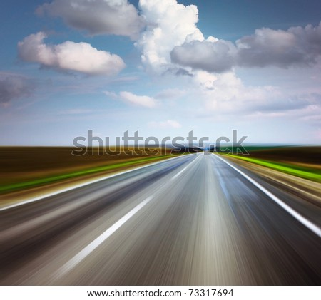 Asphalt blurry road and bright blue sky with clouds - stock photo