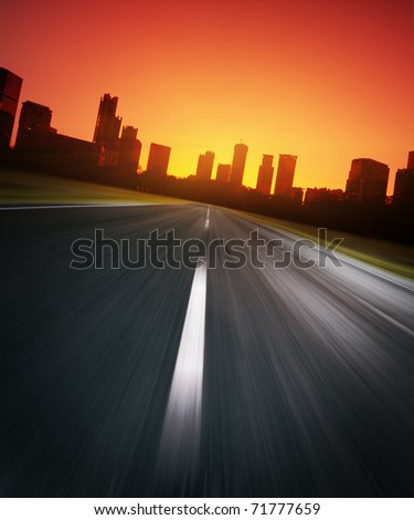 Asphalt blurry road with city silhouette on a horizon and red sunrise sky - stock photo