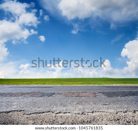 Asphalt country road and blue sky, side view. Landscape in summer day