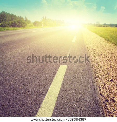 Asphalt country road at sunset. Vintage image. - stock photo