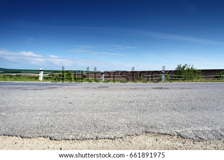 asphalt country road side view with field on background, landscape in summer day